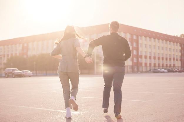 Um jovem casal corre na rua num dia de verão de mãos dadas, feriados, fim de semana, vida feliz