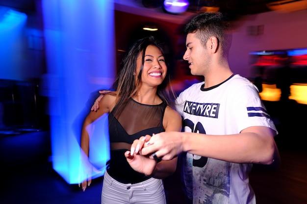 Um jovem casal dançando salsa e bachata em um clube noturno
