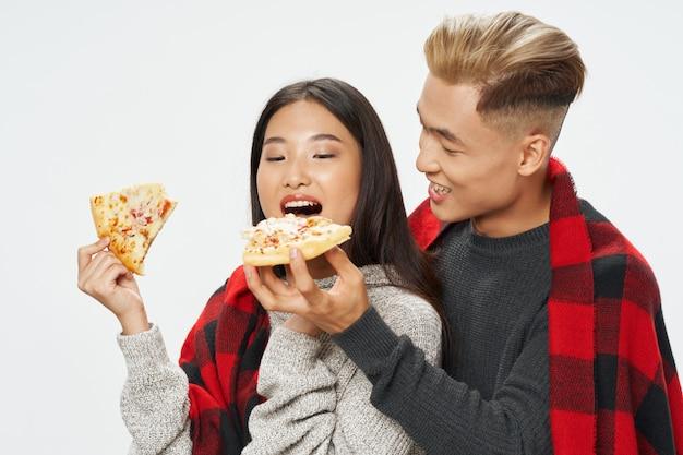Um jovem casal de aparência asiática alegre coberto de um cobertor xadrez e comendo pizza
