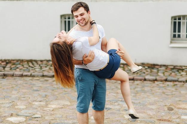 Um jovem casal de bermuda e camiseta branca andando na cidade
