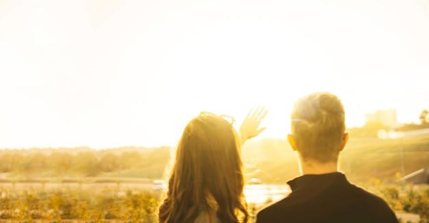 Um jovem casal de homem e mulher olhando para o céu e cobrindo o sol com as mãos, beleza de raios de sol
