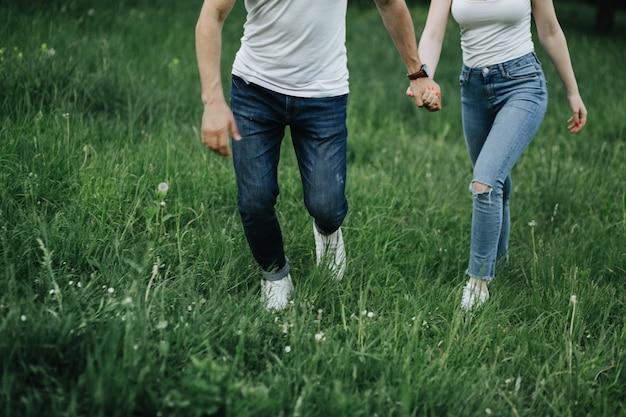 Um jovem casal de mãos dadas e andando na grama