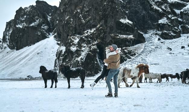 Um jovem casal de turistas se diverte entre as pastagens de cavalos selvagens nas encostas de montanhas cobertas de neve.