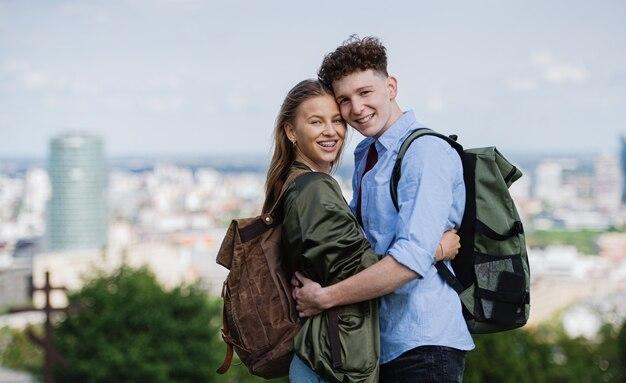 Um jovem casal de viajantes na cidade de férias, olhando para a câmera. paisagem urbana em segundo plano.