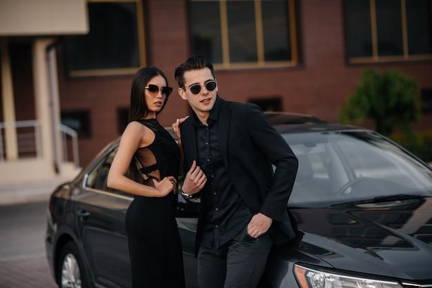 Um jovem casal elegante de preto fica perto do carro ao pôr do sol. moda e estilo