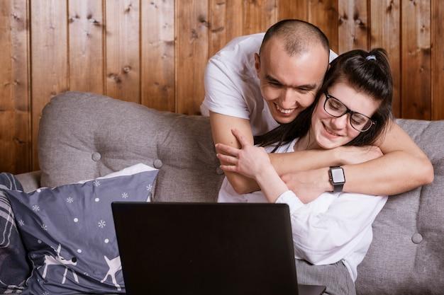 Um jovem casal em casa sentado no sofá se comunicando on-line via laptop com parentes