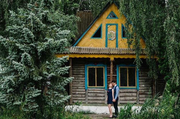 Um jovem casal em pé e abraçando perto de uma casa velha de madeira em uma ilha na floresta entre árvores