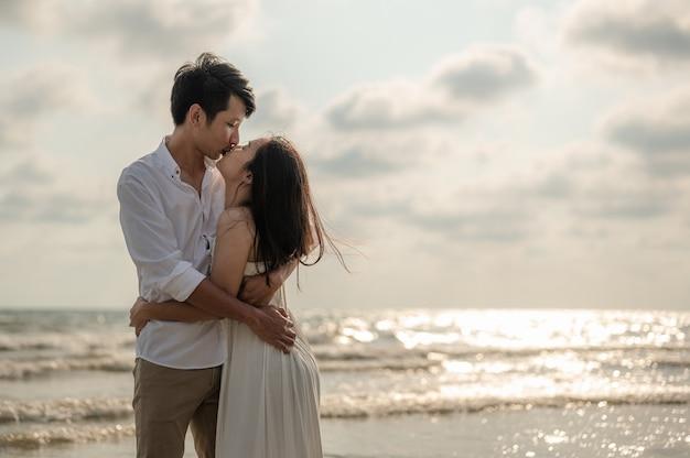 Um jovem casal em pé se beijando na praia ao pôr do sol da noite. verão apaixonado. dia dos namorados