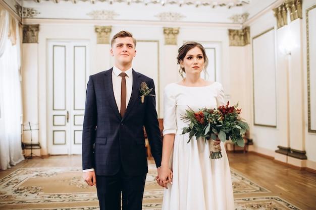 Um jovem casal em vestidos de noiva em uma antiga mansão.