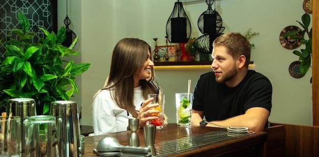 Um jovem casal encantador sentado com um coquetel no bar, conversando e se divertindo