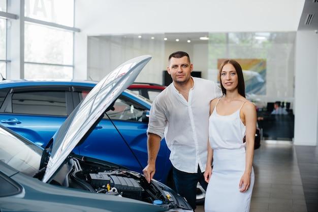Um jovem casal escolhe um carro novo na concessionária e consulta um representante da concessionária. carros usados para venda. realização dos sonhos.