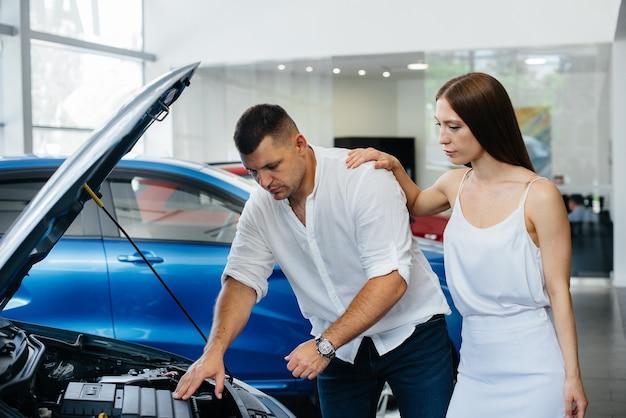 Um jovem casal escolhe um carro novo na concessionária e consulta um representante da concessionária.