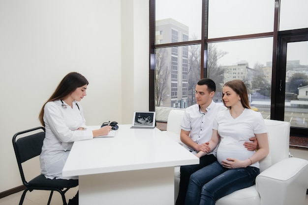Um jovem casal esperando um bebê consultar um ginecologista após um ultra-som.