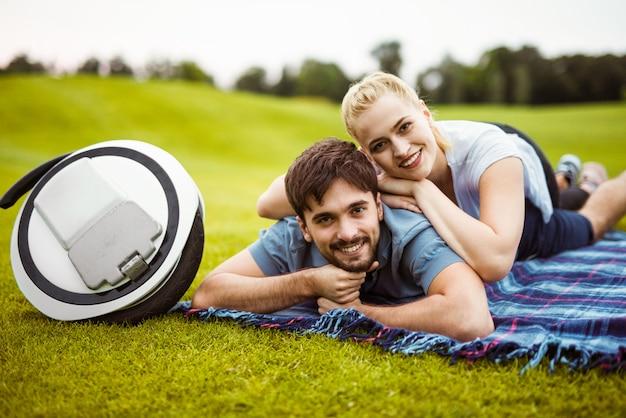 Um jovem casal está deitado na grama, sobre o cobertor.