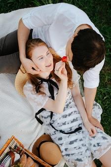 Um jovem casal está descansando no parque em um cobertor comendo morangos frescos, uma garota romântica e um cara fazem um piquenique ao ar livre fora da cidade