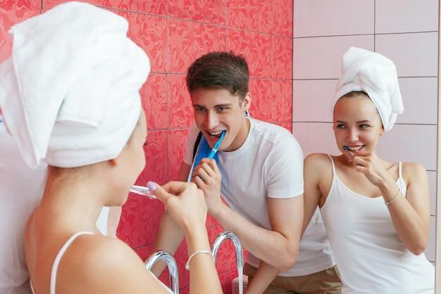 Um jovem casal está escovando os dentes. casal brincando no banheiro. fotografia de estilo de vida