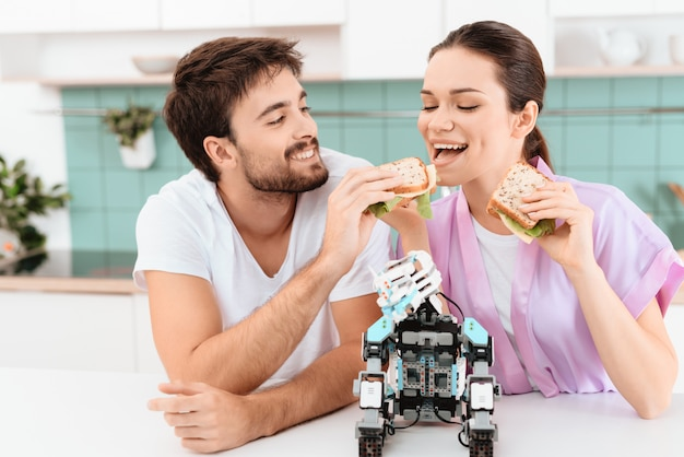 Um jovem casal está sentado na cozinha e garota desgrenhada.