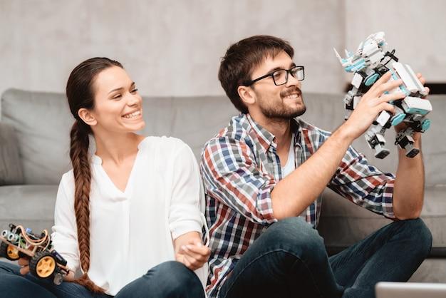 Um jovem casal está sentado no chão da sala de estar