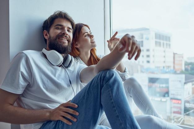 Um jovem casal está sentado perto da janela com fones de ouvido juntos em apartamentos