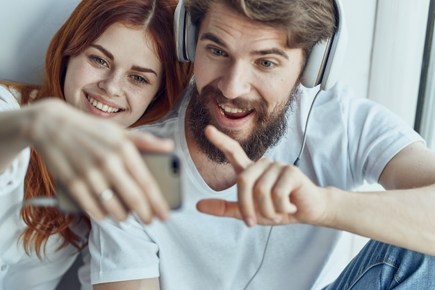Um jovem casal está sentado perto da janela com fones de ouvido juntos tecnologia de apartamentos