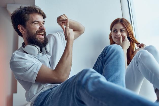 Um jovem casal está sentado perto da janela com fones de ouvido, romance, alegria