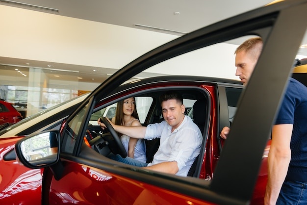 Um jovem casal feliz escolhe e compra um carro novo em uma concessionária. comprando um carro novo.