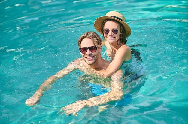 Um jovem casal feliz nadando em uma piscina