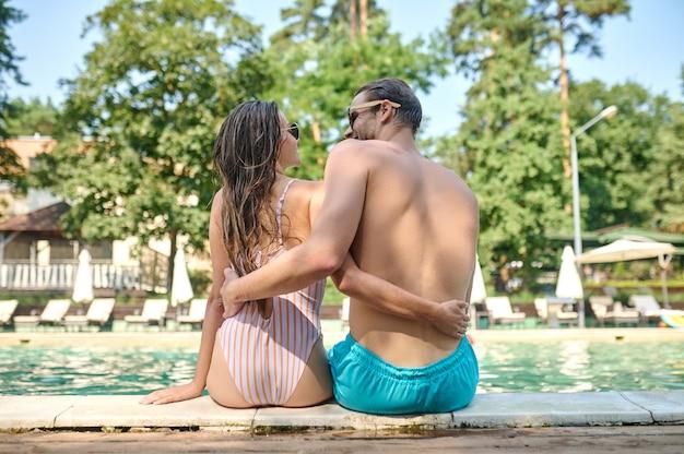 Um jovem casal feliz perto da piscina se sentindo feliz e relaxado