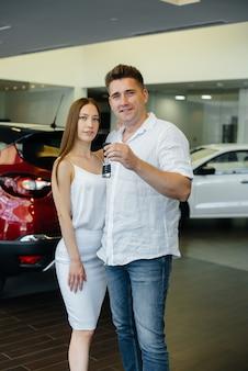 Um jovem casal feliz tem o prazer de comprar um carro novo. compra de carro.