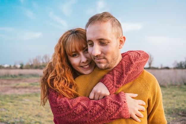 Um jovem casal feliz vestindo blusas quentes em pé no campo sob um céu azul