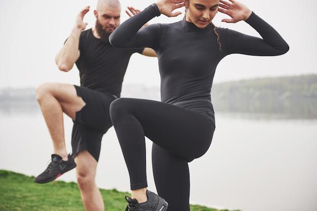 Um jovem casal gosta de praticar esportes pela manhã ao ar livre. aquecer antes do exercício
