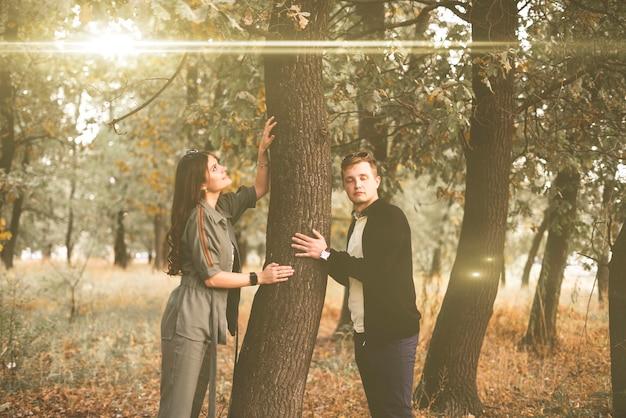 Um jovem casal hag a árvore na floresta, conceito de conexão de pessoas com a natureza