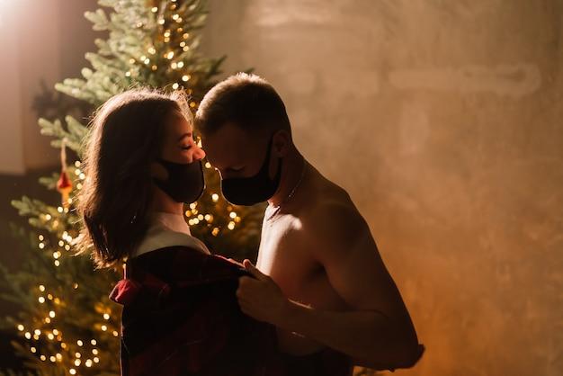 Um jovem casal homem e mulher com máscaras médicas descartáveis sob uma árvore de natal.