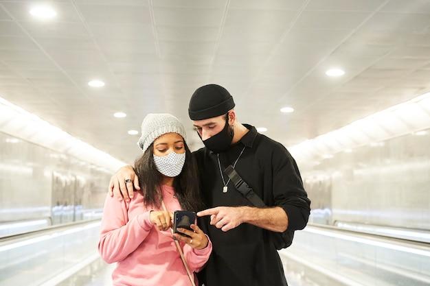 Um jovem casal interracial de amantes com máscaras e gorros de lã caminhando por um corredor de metrô
