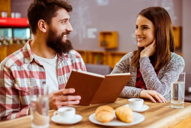 Um jovem casal lê o menu para fazer um pedido.