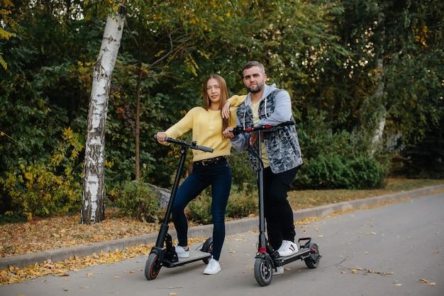 Um jovem casal lindo anda de scooters elétricos no parque em um dia quente de outono.