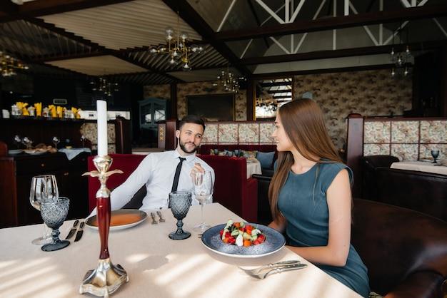 Um jovem casal lindo está almoçando em um bom restaurante. atendimento ao cliente na área de catering.