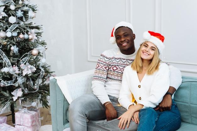 Um jovem casal multiétnico com chapéu de papai noel está sentado em um sofá em um interior bem iluminado ao lado de uma árvore