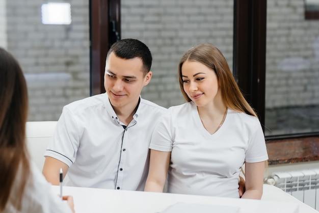 Um jovem casal na consulta de um ginecologista após um ultra-som. gravidez e cuidados de saúde.