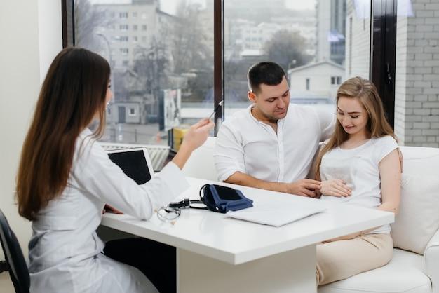 Um jovem casal na consulta de um ginecologista após um ultrassom. gravidez e cuidados de saúde.