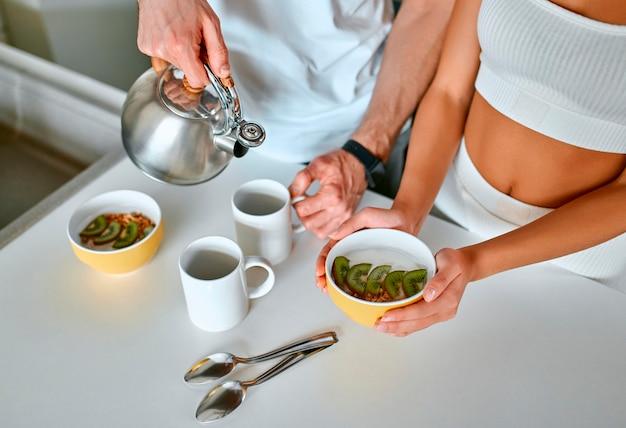 Um jovem casal na cozinha toma café da manhã e bebe chá pela manhã. nutrição esportiva saudável, perda de peso.