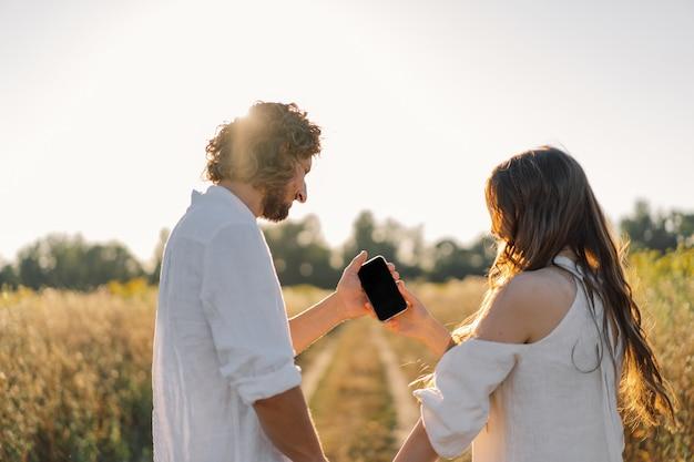 Um jovem casal na natureza olha para o telefone.
