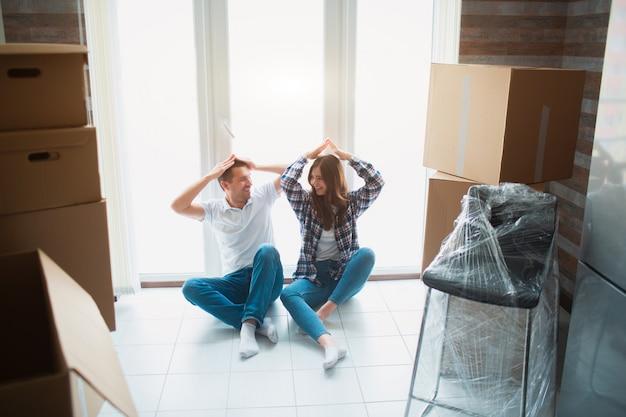 Um jovem casal na sala de estar em casa está sentado perto da janela. eles estão felizes com o novo lar. movendo-se, comprando uma casa, conceito de apartamento.