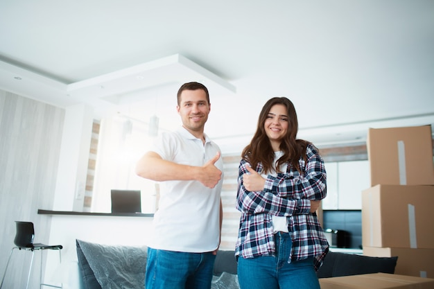 Um jovem casal na sala de estar em casa fica perto de caixas desembaladas, levanta o polegar e olha para a câmera. eles estão felizes com o novo lar. movendo-se, comprando uma casa, conceito de apartamento.