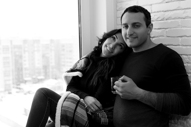 Um jovem casal olha pela janela de um apartamento novo