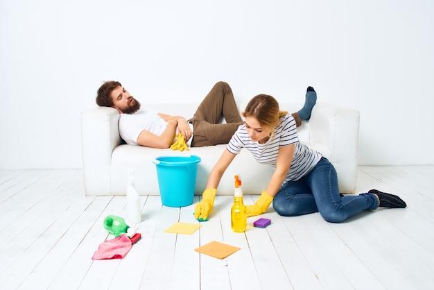 Um jovem casal perto do sofá trapos detergentes esponjas prestação de serviços