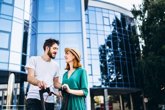 Um jovem casal romântico com scooters elétricos em um encontro, andando na cidade. jovem de chapéu e homem desfrutar de um passeio