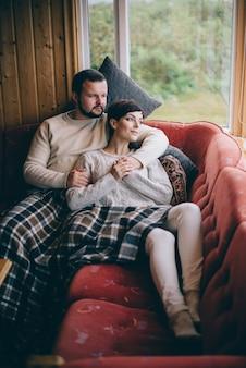 Um jovem casal romântico deita-se no sofá em casa durante a quarentena. conceito de auto-isolamento.
