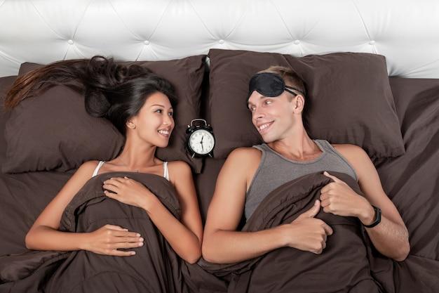 Um jovem casal satisfeito está deitado na cama, um despertador entre eles