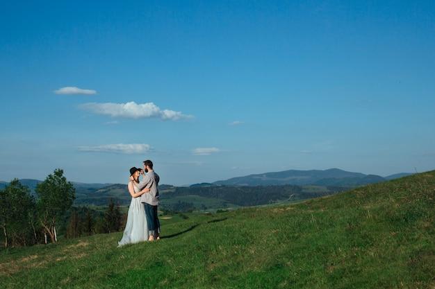 Um jovem casal se abraça nas montanhas